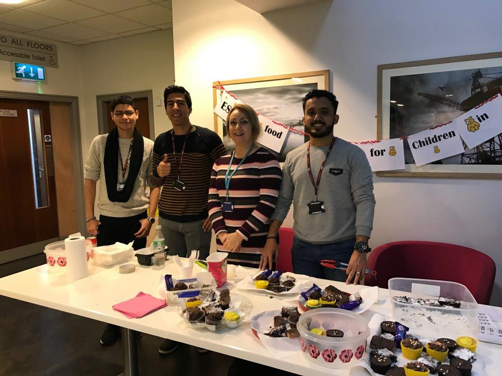 3 Wirral Met Students and 1 Staff Member standing by a table while volunteering for a Children in Need