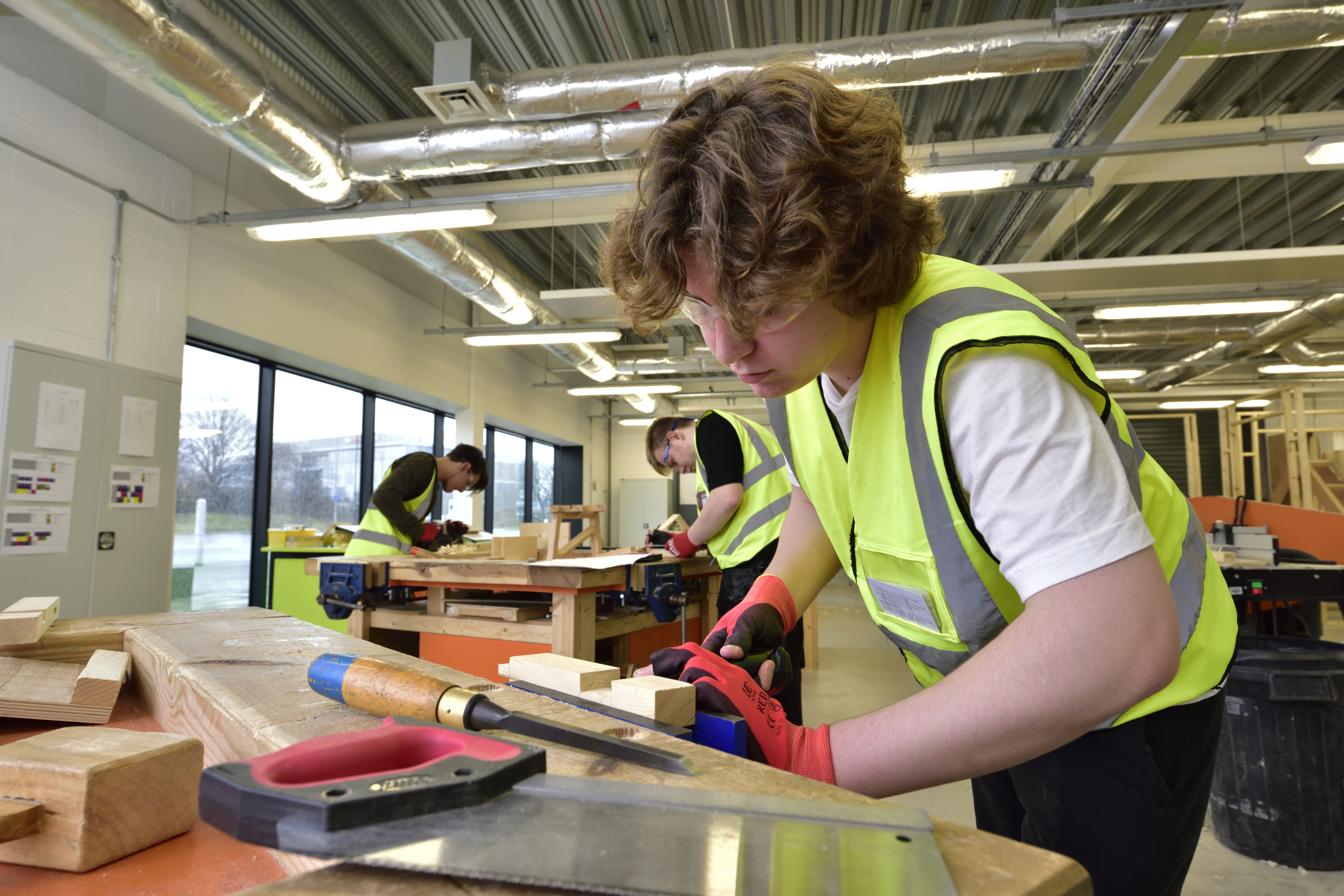 Wirral Met joinery student working in a Hi-Vis jacket at the Wirral Waters campus