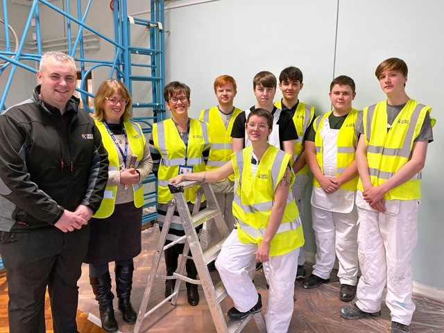 painting and decorating students and apprentice in white overalls and high vis vests stood in school next to teachers and employer