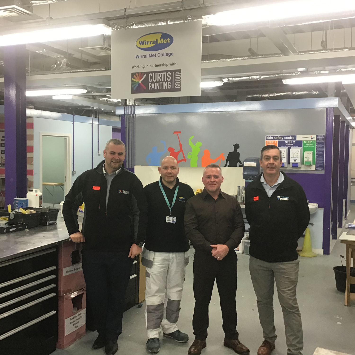 four men stood in the painting and decorating workshop at Wirral Met College