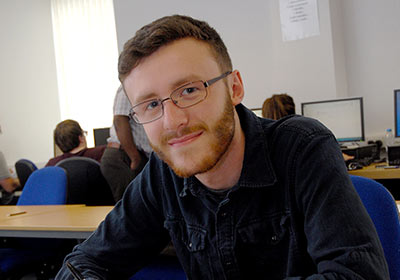 Male Accounting And Professional Studies CPD Student Sat In A Classroom Wearing Glasses
