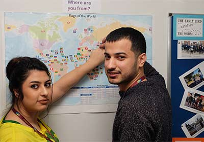 Two ESOL CPD Course Students Pointing At World Map In Classroom