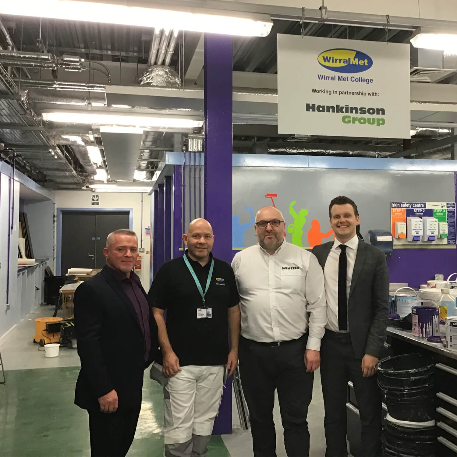 Four men stood in painting and decorating workshop at Wirral Met College