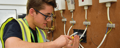 Apprentice electrician Michael Bayley, wearing glasses and high vis, installing wiring systems as part of his apprenticeship with Magenta Living