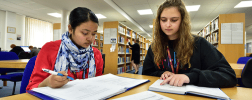 Two girls studying in the Library at Wirral Met College