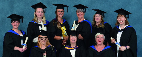 Higher Education graduates wearing gowns posing for group picture