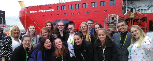 A group photo of Wirral Met College students and staff standing behind a red ship at the RRS Sir David Attenborough naming ceremony