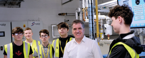 Metro Mayor Steve Rotheram standing next to Wirral Met Students wearing Hi-Vis Jackets